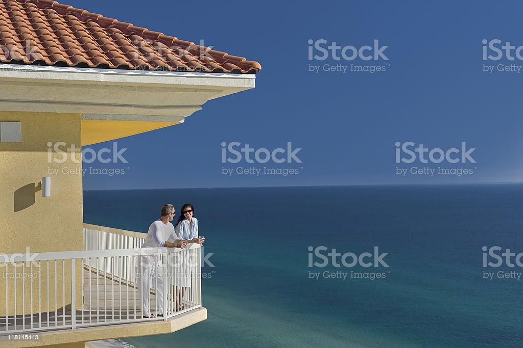 Couple Talking On Porch Overlooking Ocean stock photo