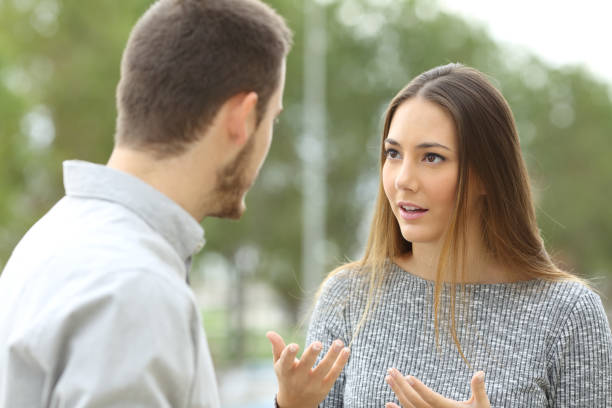 Couple talking outdoors in a park stock photo