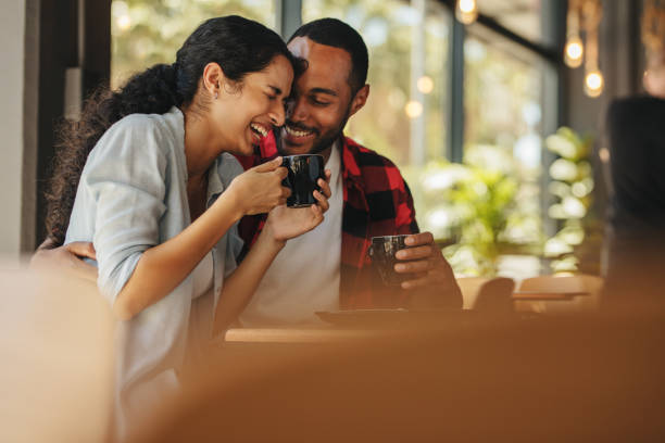 Couple talking over a cup of coffee at cafe stock photo