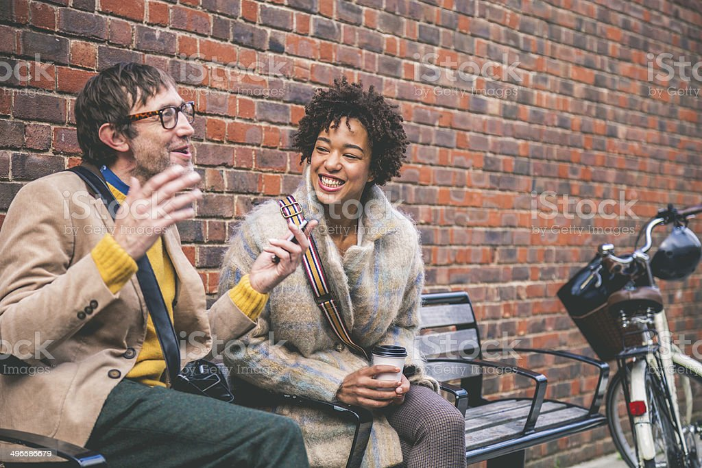 Couple talking seated on a bench stock photo