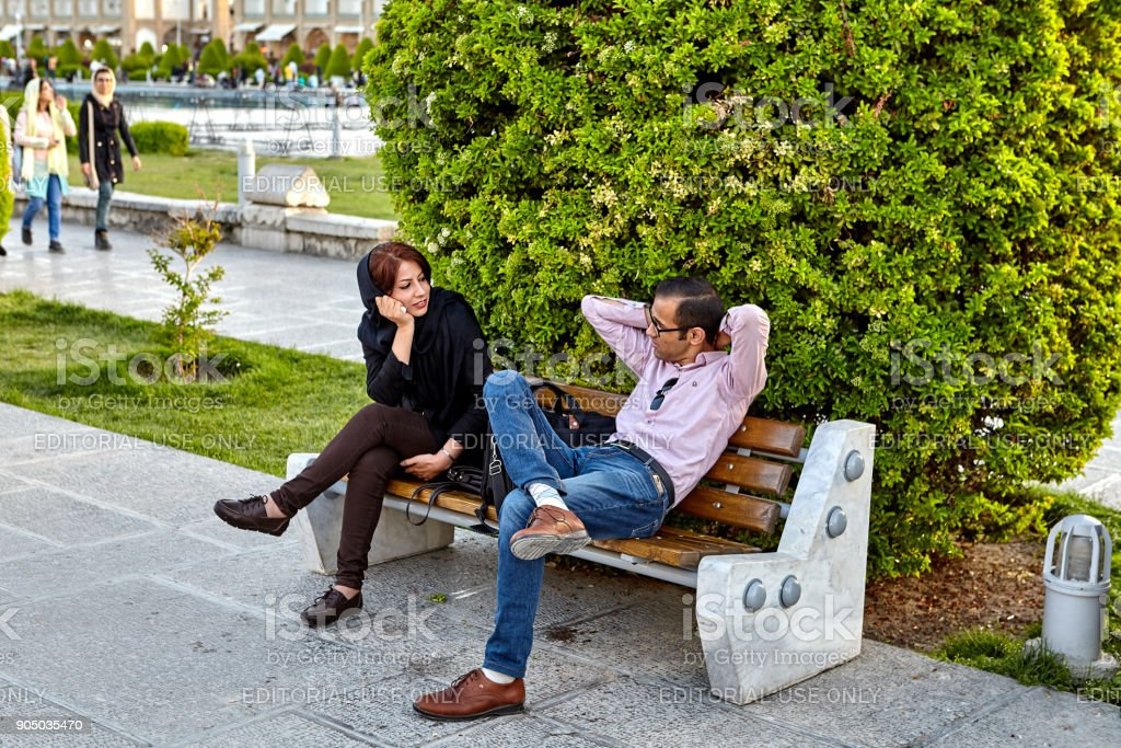 Couple talking, sitting on bench in Naghshe Jahan square, Iran. stock photo