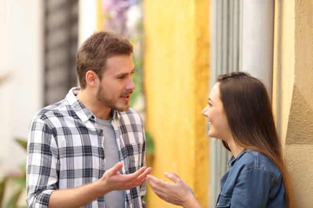 Couple talking standing in a colorful street stock photo