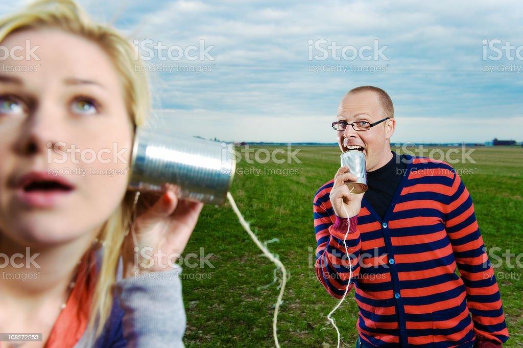 Couple talking through Tin-Can phones royalty-free stock photo