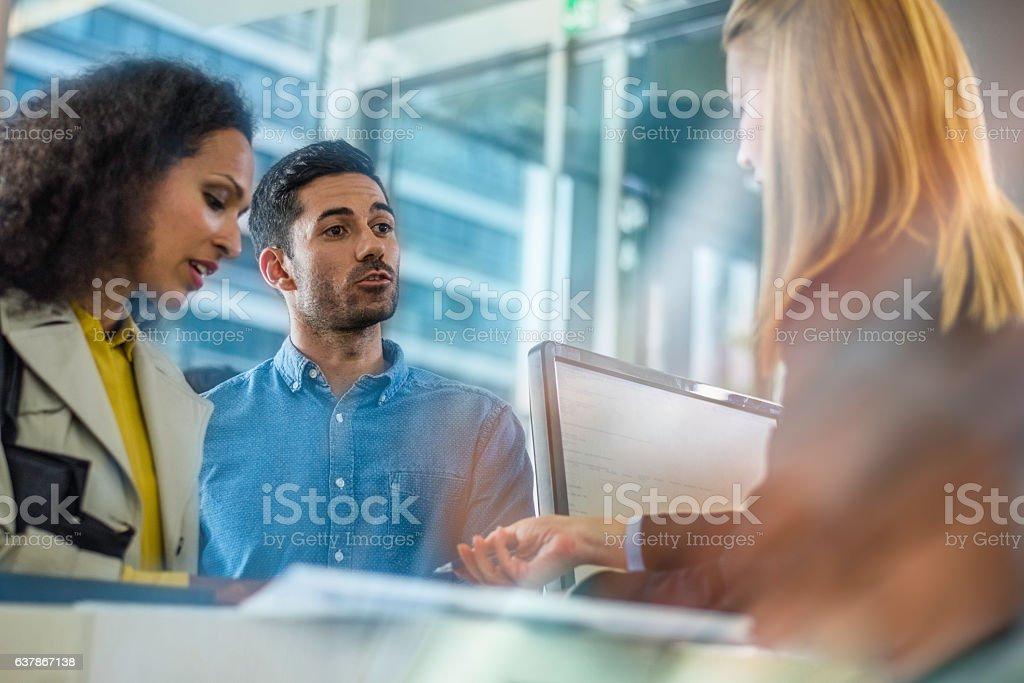 Couple talking to a bank teller - Photo