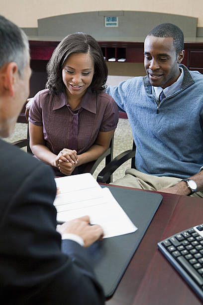 couple talking to bank manager - bankers stock photos and pictures
