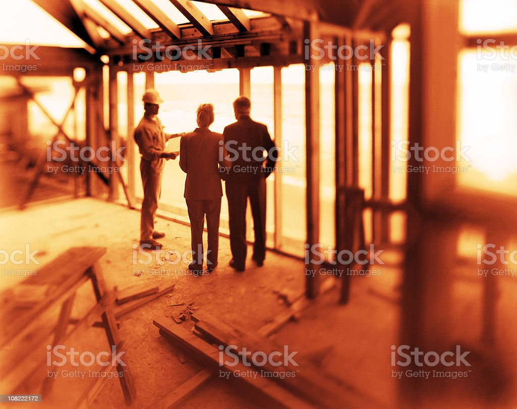 Couple Talking to Construction Worker in Framework of House royalty-free stock photo