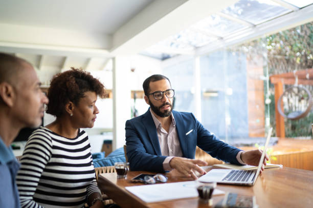 Couple talking to finance advisor at home stock photo