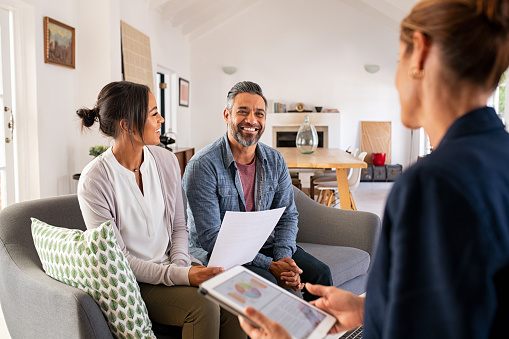 Happy mature couple discussing investments with financial broker during meeting at home. Happy middle eastern man and hispanic woman discussing about financial planning with consultant at home. Financial consultant presenting new investment plan to smiling mature couple at home.