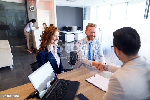 istock Couple talking to loan officer and shaking hands 674650850