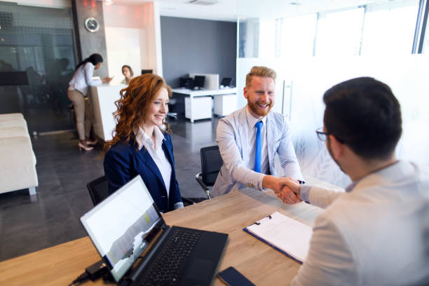 Couple talking to loan officer and shaking hands stock photo