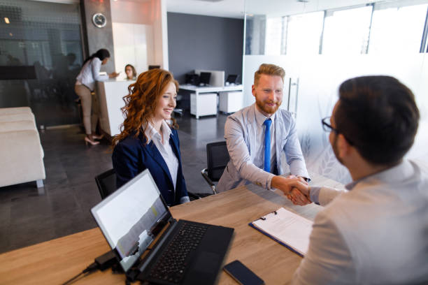 couple talking to loan officer and shaking hands - bankers stock photos and pictures