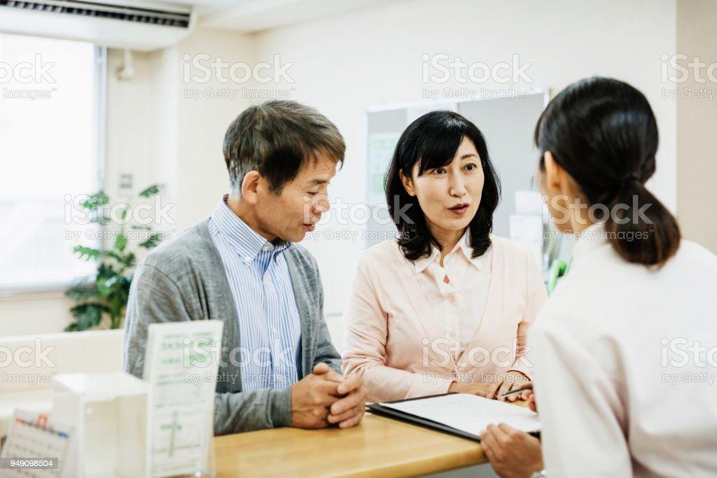 看護師にカップルの話や病院でのフォームの記入 ストックフォト