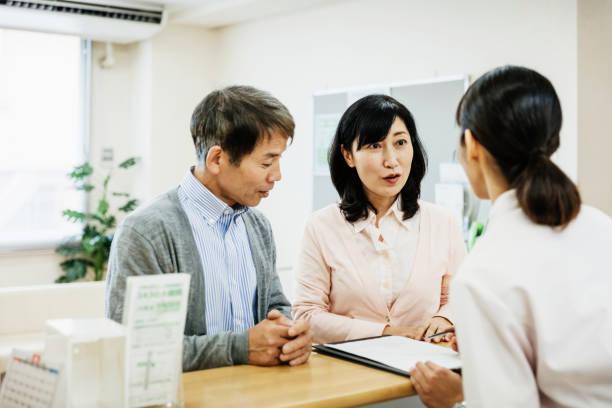 Paar im Gespräch mit Krankenschwester und Ausfüllen von Formularen im Krankenhaus – Foto