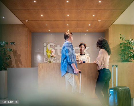 istock Couple talking to receptionist at hotel lobby 951445196