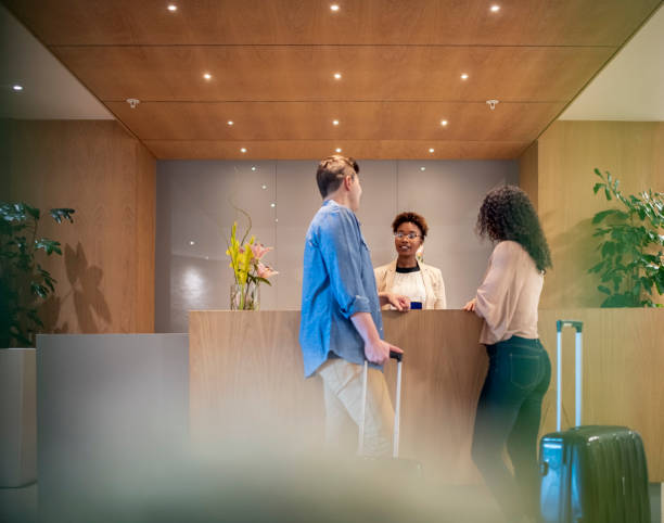 couple talking to receptionist at hotel lobby - receptionist stock photos and pictures