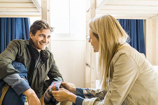 couple talking while sitting on bunkbeds in train - etagenbett weiss stock-fotos und bilder