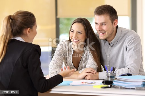 istock Couple talking with a real estate agent 820868562