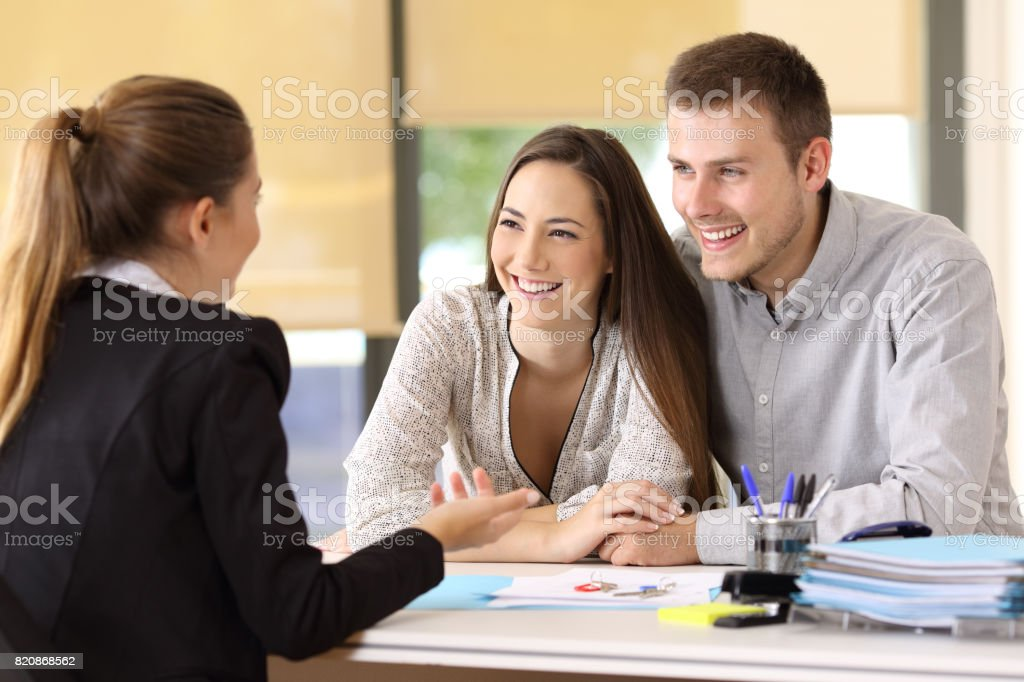 Couple talking with a real estate agent stock photo