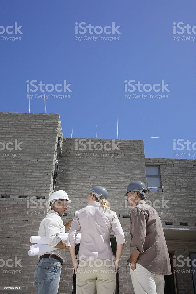 Couple talking with architect at new construction site royalty-free stock photo