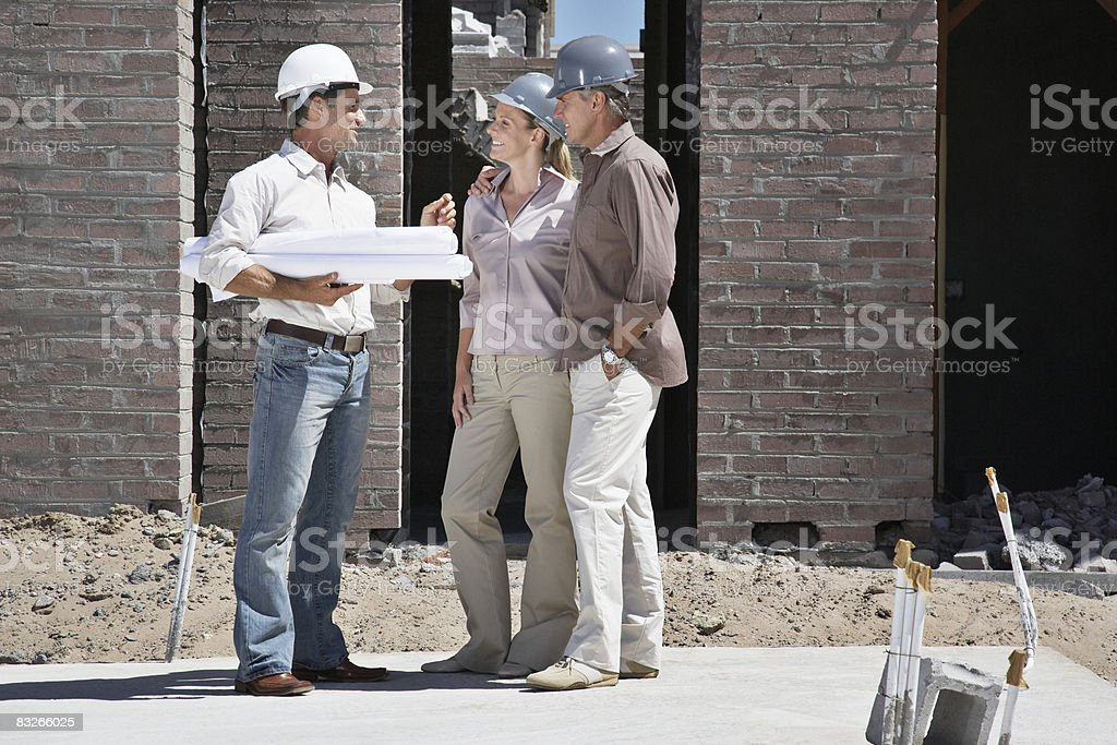 Couple talking with foreman on construction site stock photo