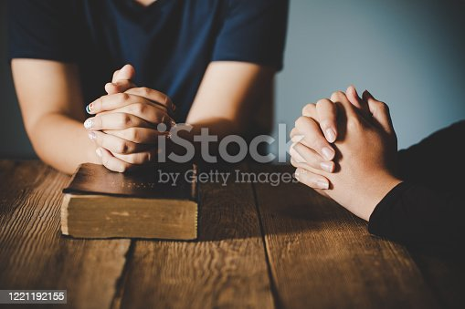 Couple teen boy and girl are pray together on wooden table with the light from side with copy space for your text