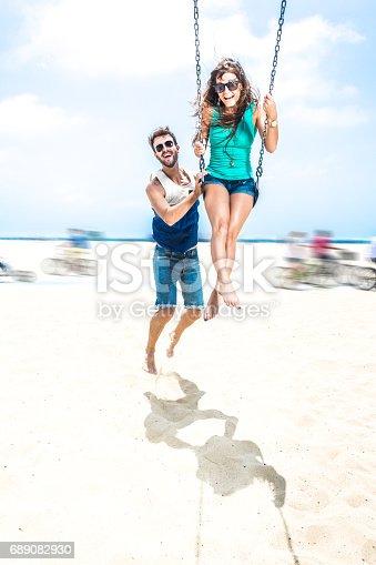 istock Couple teetering on swings LA beach 689082930