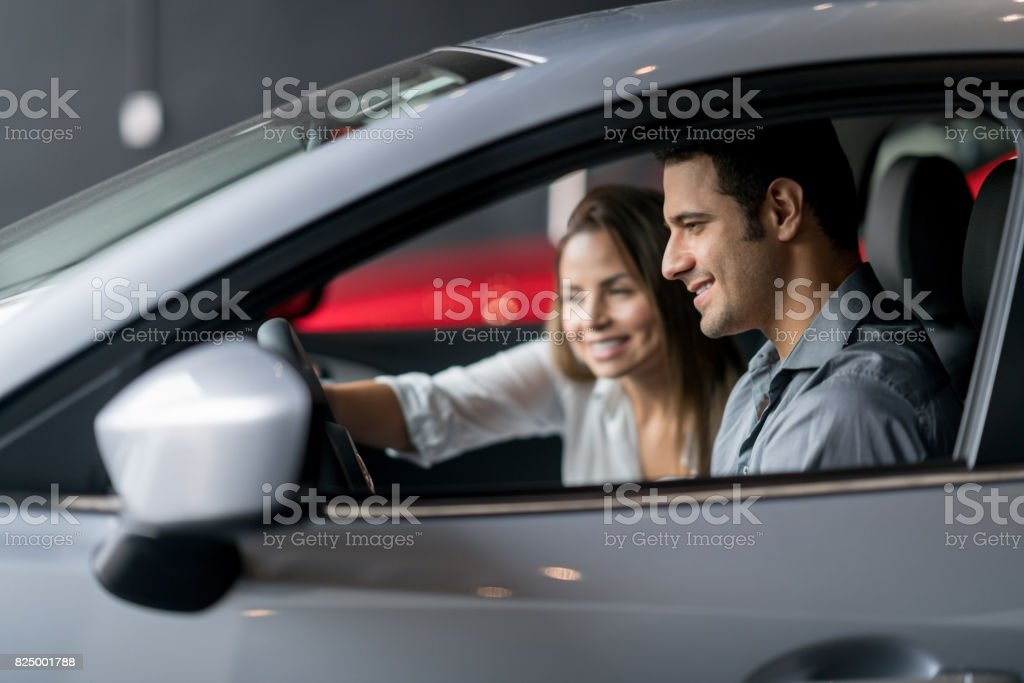 Couple test driving a car at the dealership stock photo