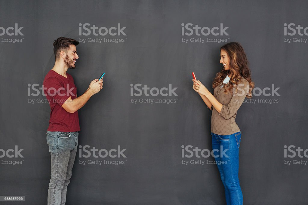 Couple texting in front of empty blackboard stock photo