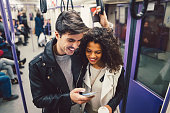 Young couple using smartphone while traveling with the subway