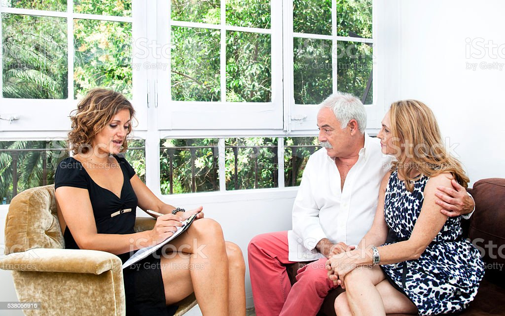 Mature-senior couple at home with a female therapist or advisor.