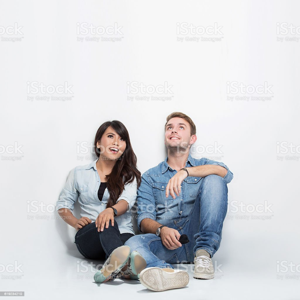 Couple thinking looking up and sitting on the floor stock photo