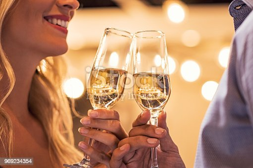 Man and woman toasting champagne flutes under light bulb outdoor. Closeup of boyfriend and girlfriend hands toasting glasses of white wine to celebrate their anniversary. Detail of party celebration.