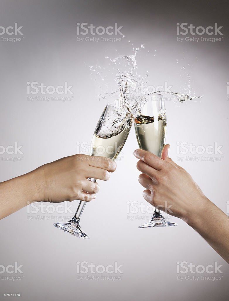 Couple toasting champagne flutes and spilling royalty-free stock photo