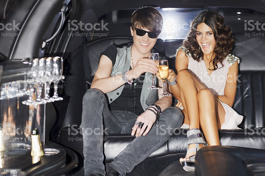 Couple toasting each other in limo stock photo