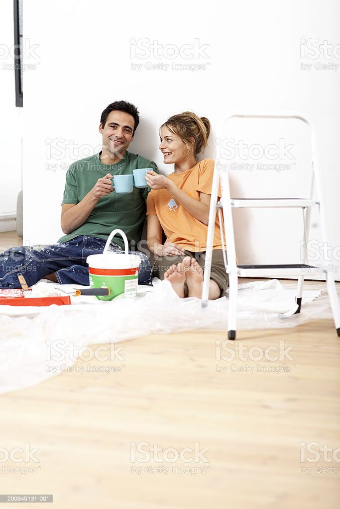 Couple toasting mugs, sitting on floor by paint and step ladder royalty-free stock photo