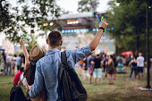 Young caucasian couple toasting on a music festival.
