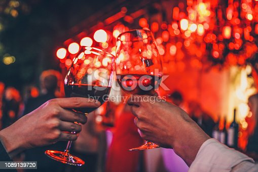 Detail of two hands cheering with glasses of  red wine on dinner date for two. Romantic lights background. Love and food concept glasses in vibe plant garden