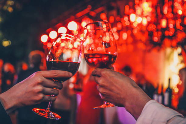 Couple toasting wine glasses Detail of two hands cheering with glasses of  red wine on dinner date for two. Romantic lights background. Love and food concept glasses in vibe plant garden date night romance stock pictures, royalty-free photos & images