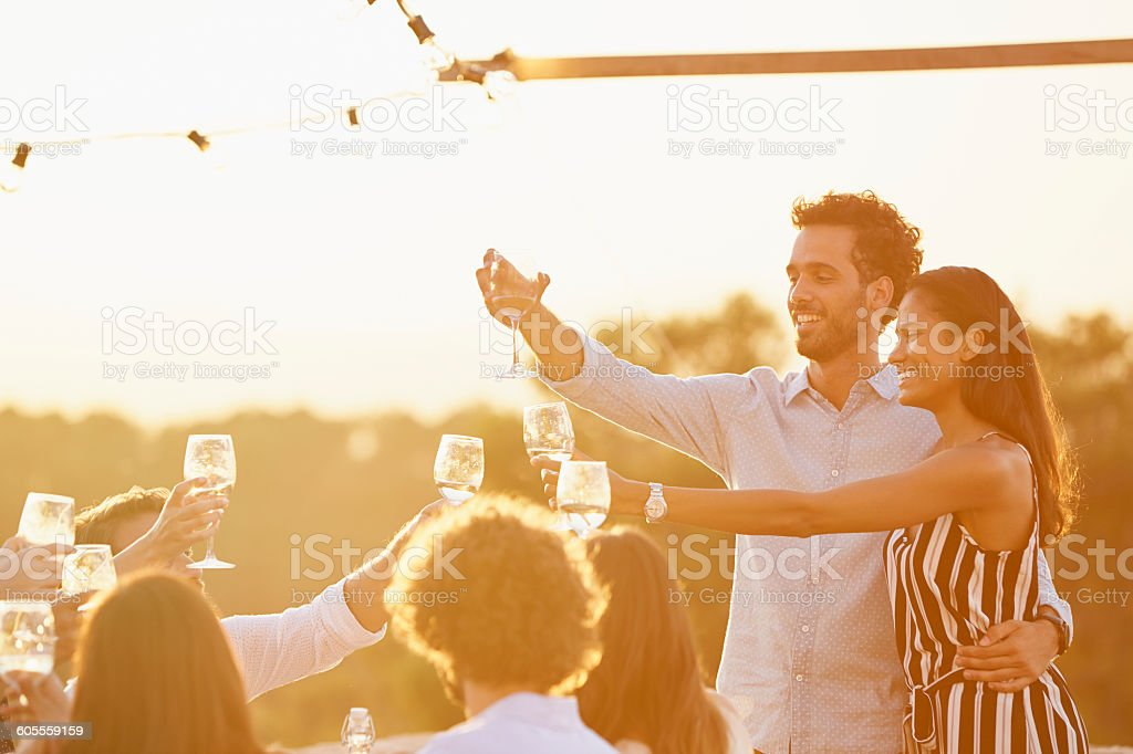 Couple toasting wine glasses with friends stock photo