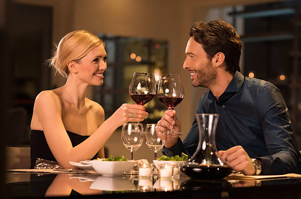 Couple toasting wineglasses Romantic young couple at restaurant raising a toast. Beautiful couple with glasses of red wine in restaurant. Couple toasting wine glasses during a romantic dinner in a gourmet restaurant. table for two stock pictures, royalty-free photos & images