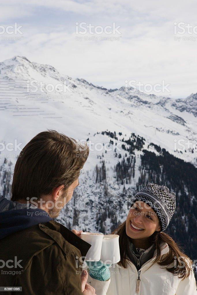 A couple toasting with a hot drink royaltyfri bildbanksbilder