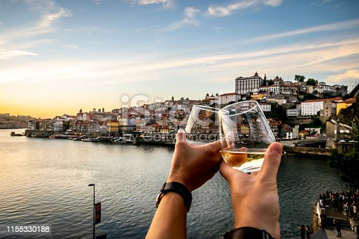 Personal perspective (POV) of a couple toasting a wine glass in the foreground of a scenic view in Porto.  Blue skies and soft white clouds roam over the Douro river between the cities of Porto and Vila Nova de Gaia display it's colourful City-line in the background.