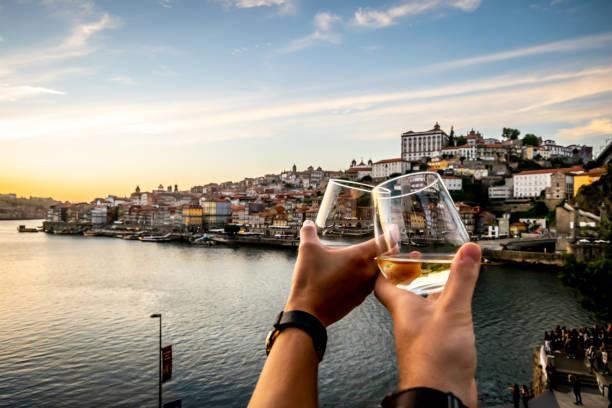 paar toasten met de rivier de douro en porto op de achtergrond bij zonsondergang. - portugal stockfoto's en -beelden
