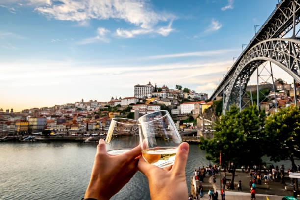 paar toasten met de rivier de douro en porto op de achtergrond bij zonsondergang. - foto's van hands stockfoto's en -beelden