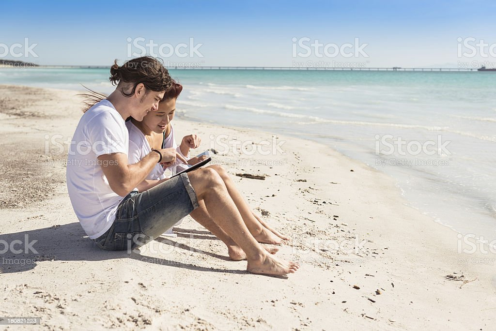 Couple togetherness surfing with tablet on the beach royalty-free stock photo