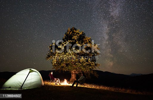 678554980istockphoto Couple tourists at night camp in mountains under starry sky 1128694502