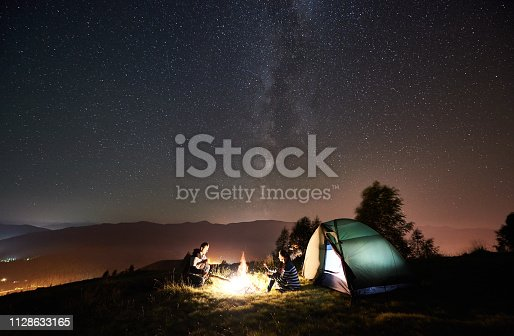 678554980 istock photo Couple tourists resting at night camping under stars 1128633165