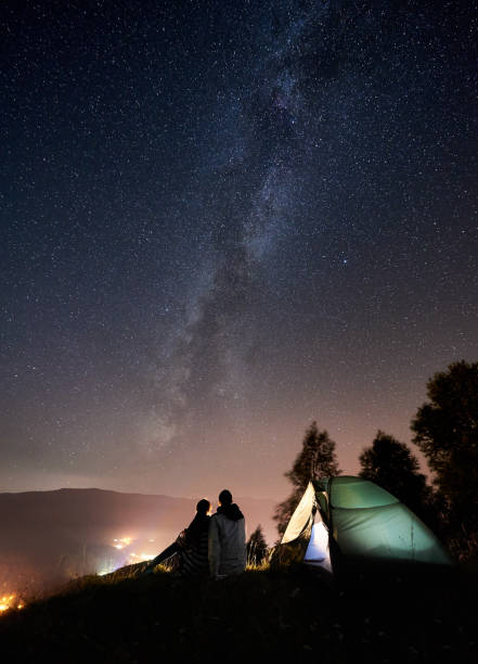 Couple tourists resting at night camping under stars Back view of young couple tourists having a rest at bonfire near illuminated tent under amazing night sky full of stars and Milky way. On background beautiful starry sky, mountains and luminous city entertainment tent stock pictures, royalty-free photos & images