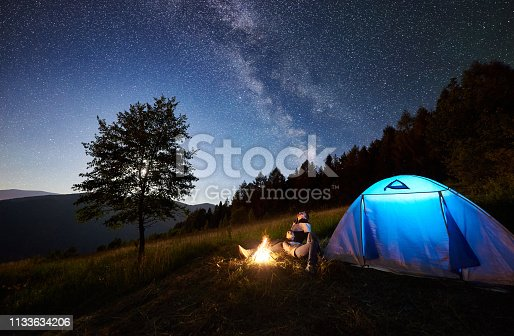 678554980 istock photo Couple tourists resting at night camping under stars 1133634206