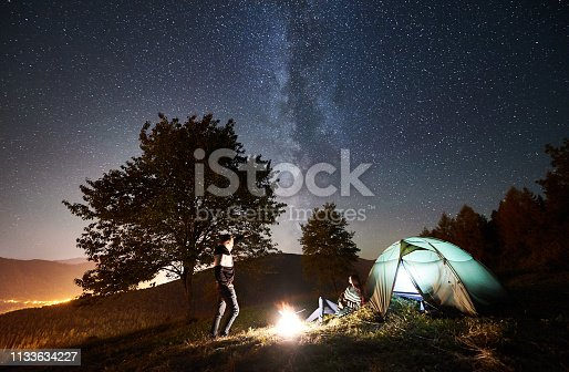 678554980 istock photo Couple tourists resting at night camping under stars 1133634227